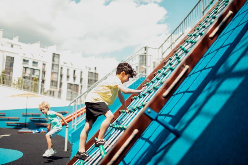 爬在运动场的男小学生一个绳梯 图库摄影