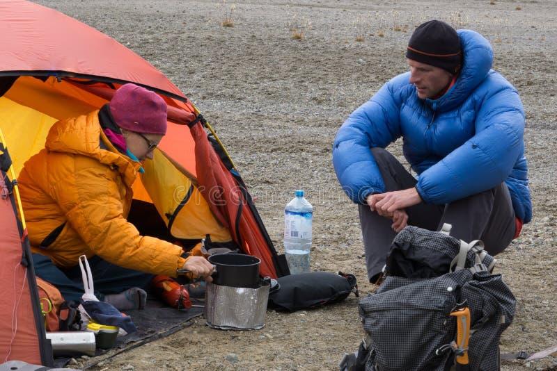 爬山者夫妇烹调晚餐在他们的在营地的帐篷在山脉布朗卡 免版税库存照片