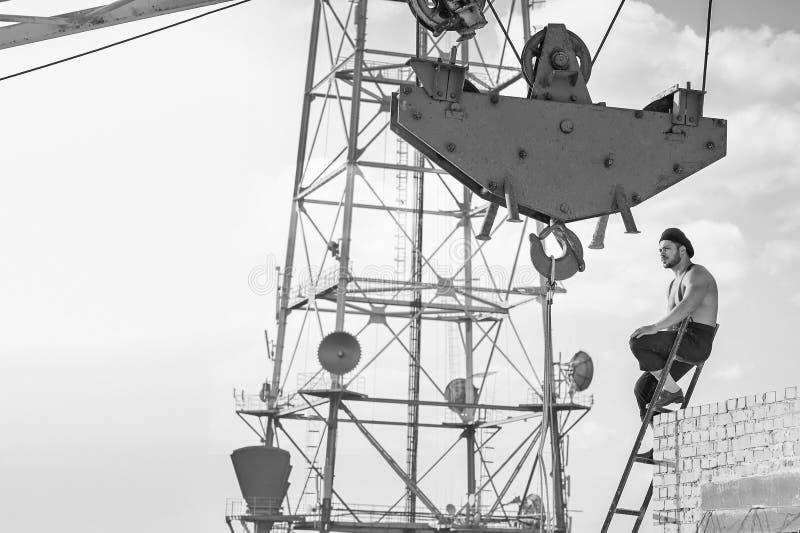 爬梯子的减速火箭的建筑工人,当工作在时 库存照片