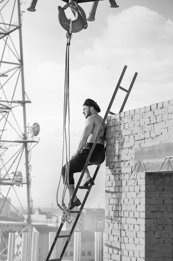 爬梯子的减速火箭的建筑工人,当工作在时 免版税库存照片