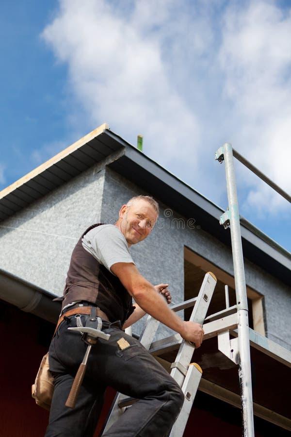 爬梯子的微笑的盖屋顶的人 免版税库存照片