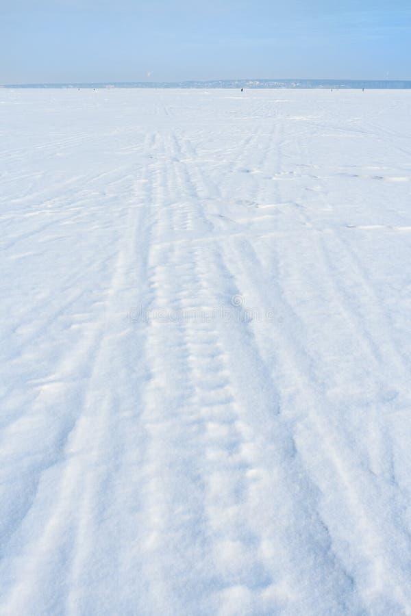 爬犁赛跑者和滑雪踪影在白色新近地下落的雪在冬天冻湖 库存照片