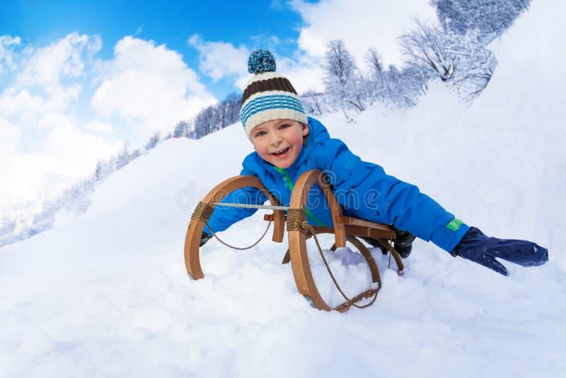爬犁幻灯片的小男孩从山 免版税库存图片