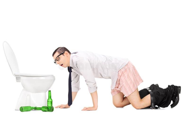 爬行到洗手间的被浪费的年轻人 免版税图库摄影