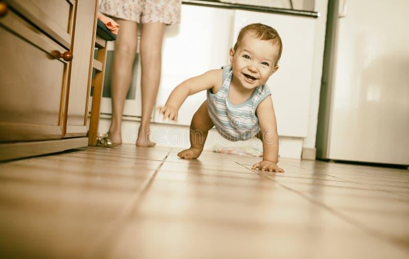 爬行在厨房里的愉快的男婴 免版税图库摄影