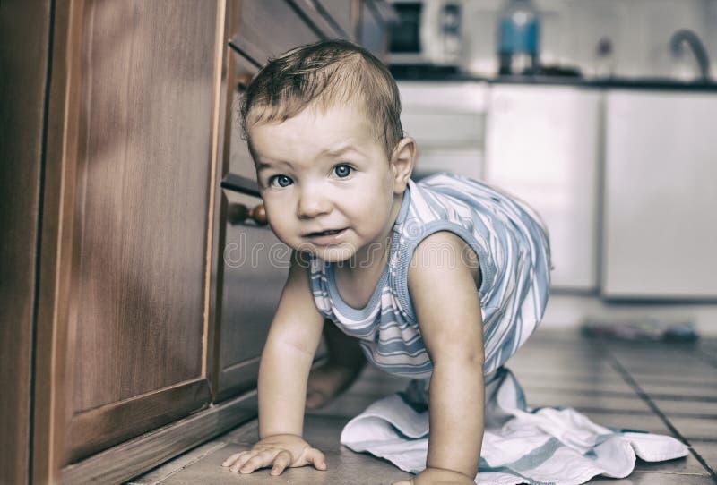 爬行在厨房里的愉快的男婴 免版税库存图片
