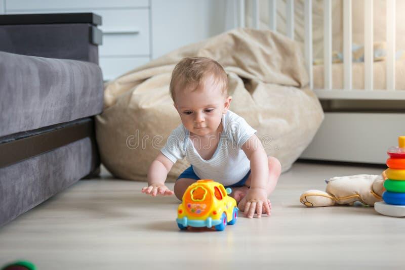爬行在地板上和到达为玩具汽车的男婴 库存照片
