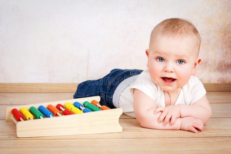 爬行在地板上的可爱的微笑的男婴 库存图片
