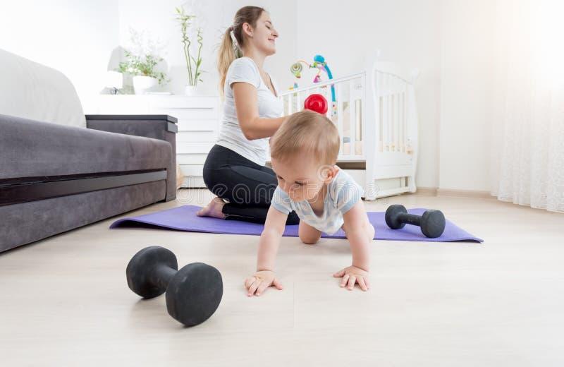 爬行在地板上的可爱的男婴,当他的母亲实践的健身在家时 库存图片