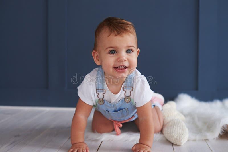 爬行在地板上的逗人喜爱的蓝眼睛的女婴 免版税库存照片