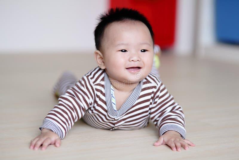 爬行在客厅楼层上的逗人喜爱的婴孩 免版税图库摄影