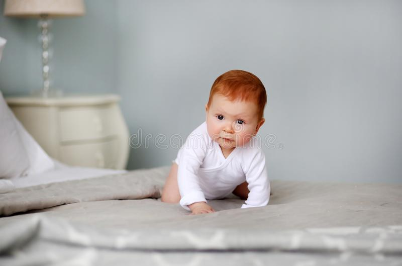 爬行在床上的白色连裤外衣的小逗人喜爱的女孩 免版税库存图片