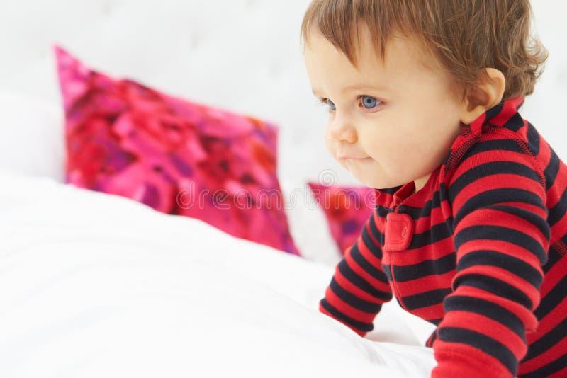 爬行在床佩带的睡衣的小孩 图库摄影