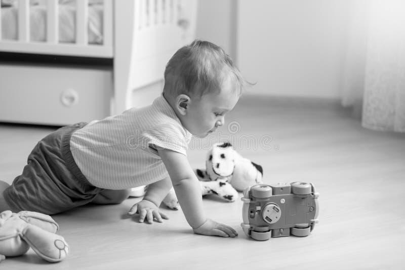 爬行在往玩具汽车的地板上的可爱的小孩男孩黑白照片  免版税库存照片