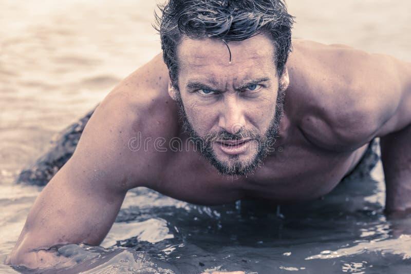 爬行在海水的英俊的赤裸上身的军队 库存照片