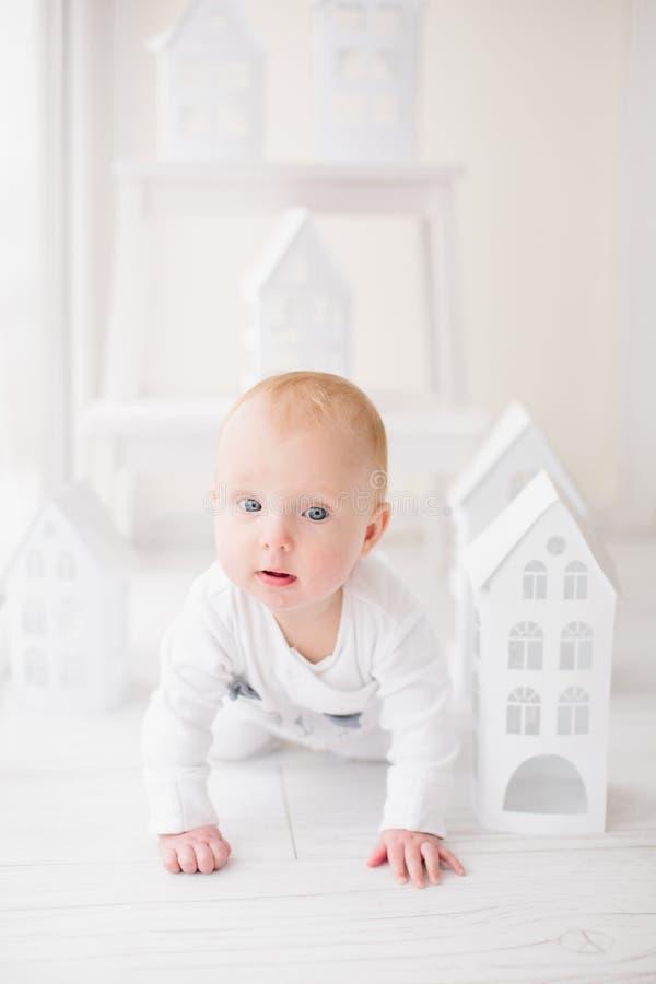 爬行在白色地板上的婴孩在白皮书房子附近 免版税库存照片