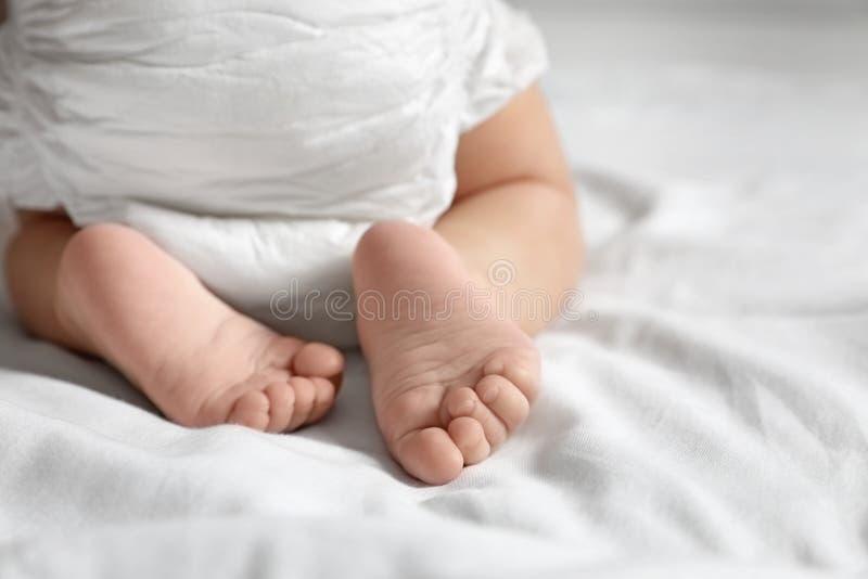 爬行在白色床单的逗人喜爱的矮小的婴孩 r 库存图片