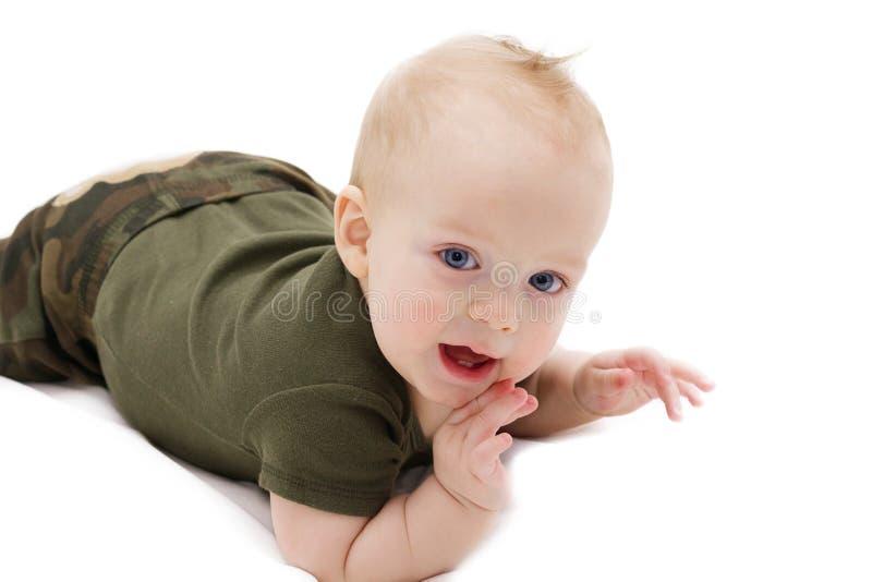 爬行在白色毯子的滑稽的蓝眼睛的男婴反对看照相机的被隔绝的白色背景 免版税库存图片