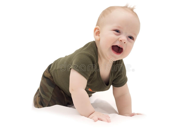 爬行在白色毯子的滑稽的笑的男婴反对被隔绝的白色背景 库存照片