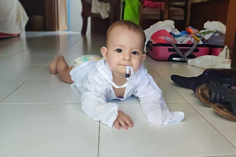 爬行在白色礼服的地板上的婴孩 ?? 她嚼一条绳索 免版税库存照片