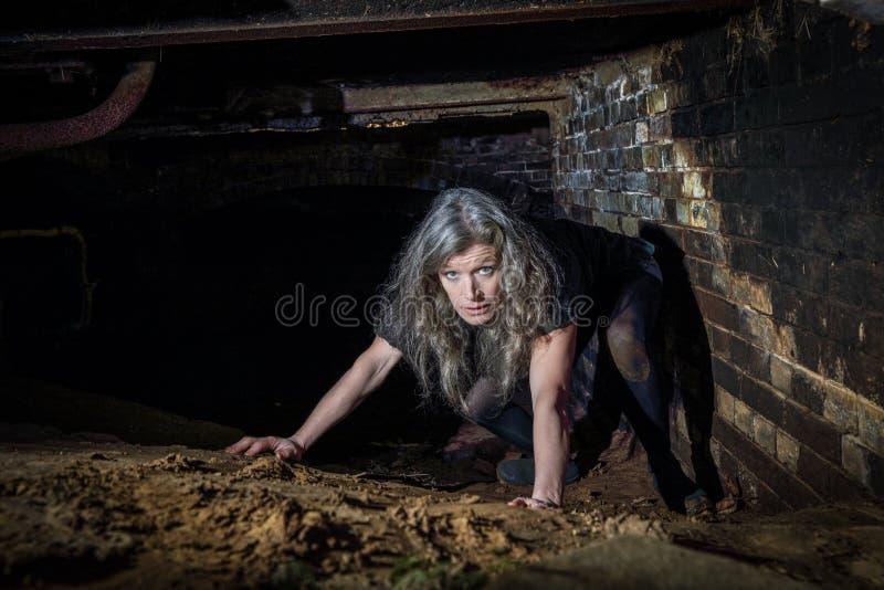 爬行在遗弃大厦的妇女 免版税库存图片