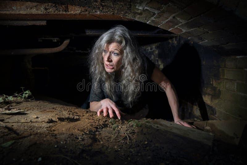 爬行在遗弃大厦的妇女 免版税库存照片