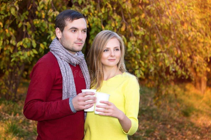 爱、关系、季节、友谊和人概念-愉快的享受与纸coff的男人和妇女金黄秋天秋季 免版税库存图片