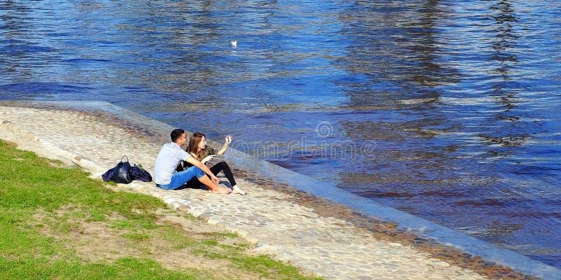 ? 爱、技术、关系、家庭和人概念-幸福微笑年轻夫妇,由河 r 免版税图库摄影