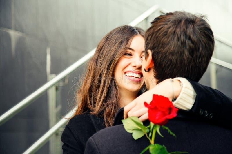 爱上一朵玫瑰的愉快的夫妇在街道上 免版税图库摄影