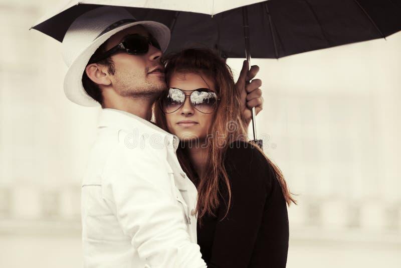 爱上伞的年轻时尚夫妇在城市街道 免版税库存照片