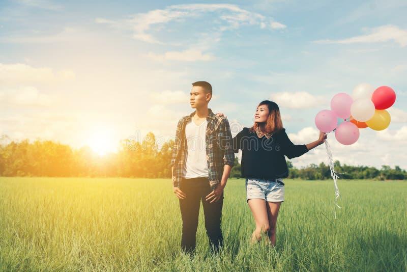 爱上气球的年轻夫妇在绿草b的手上 免版税库存照片