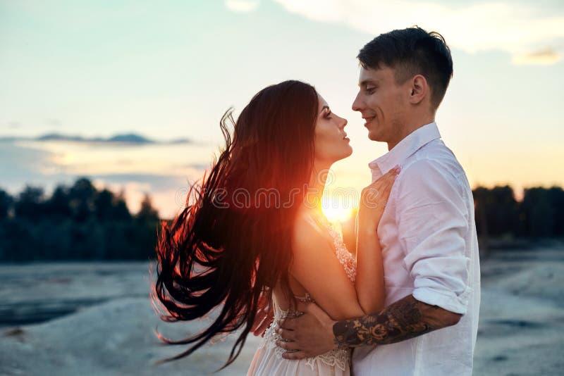 爱亲吻和拥抱在爱夫妇在日落在晚上太阳、步行通过山和小山 肉欲和柔和爱 库存照片