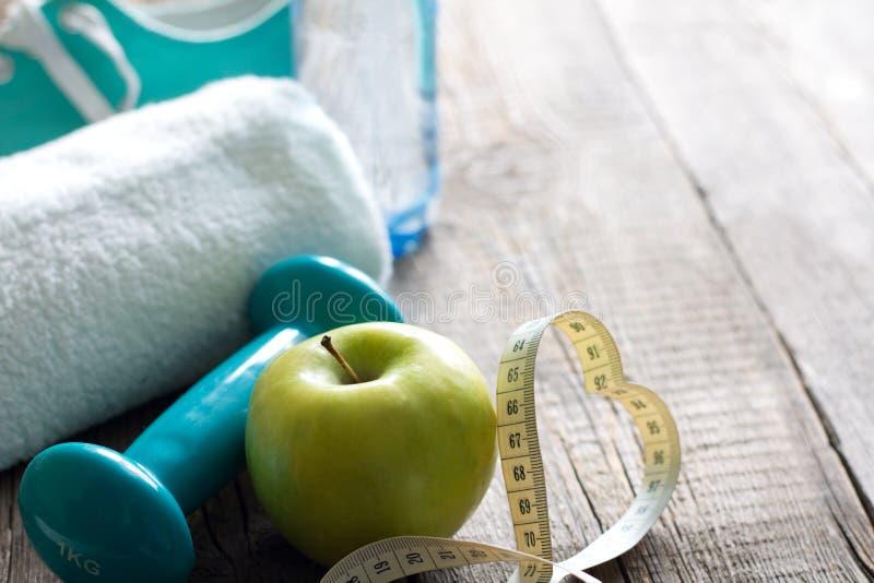 爱健身并且节食概念用心脏测量的磁带苹果和哑铃 免版税库存照片