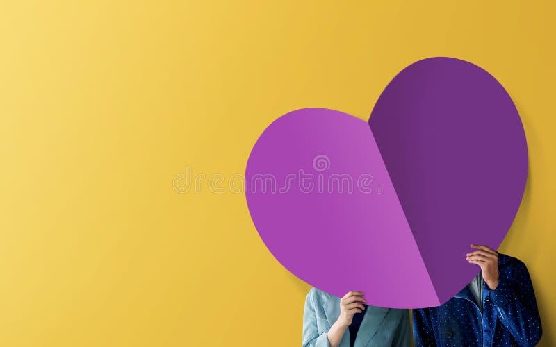 爱和情人节概念 年轻人结合站立在墙壁和被盖的面孔由纸心形 明亮的颜色口气 免版税库存图片