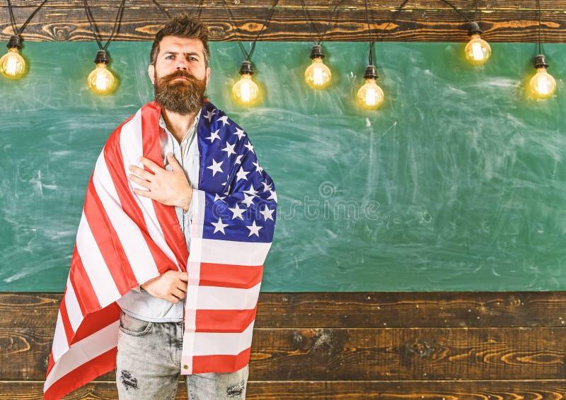 爱国教育概念 用美国国旗盖的美国老师 有胡子的在严肃的面孔的人和髭 免版税库存图片