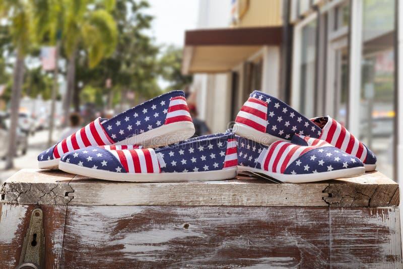 爱国美国国旗鞋子在小城商店边路前面的显示 库存照片