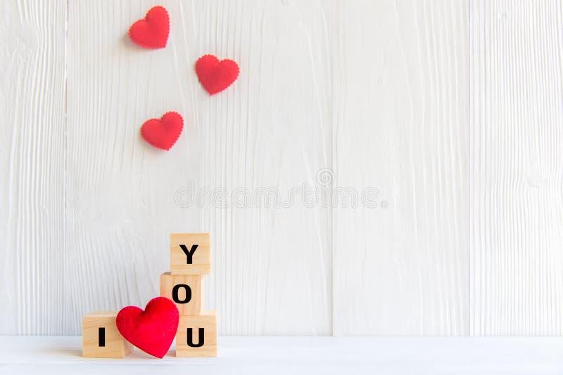 爱在与红色心脏,白色木背景的木块写的消息 库存照片