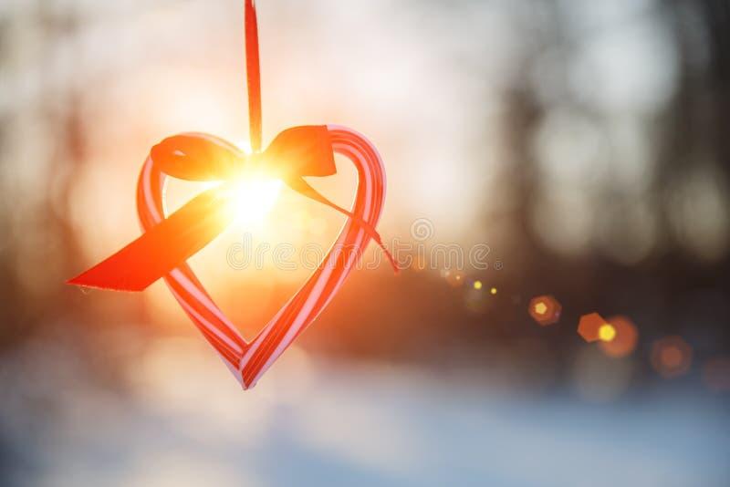 爱在冬天 心形的标志情人节 心脏用手,感觉和生活方式概念在日落光 库存图片