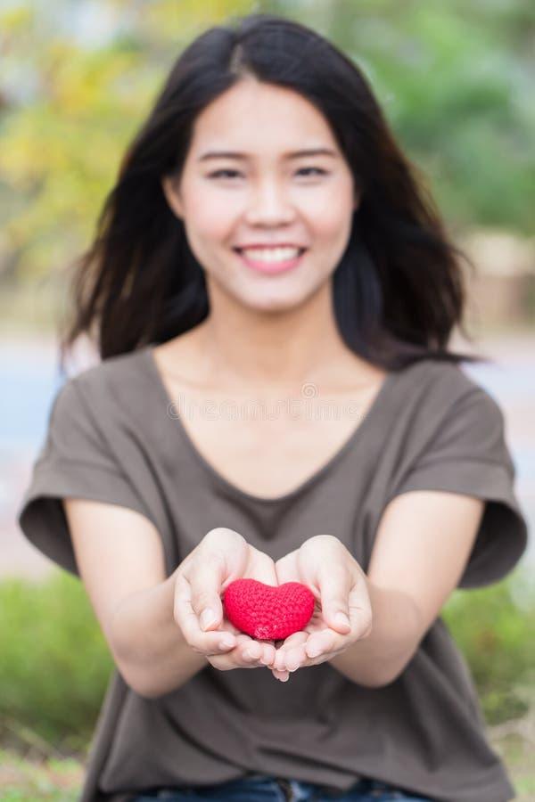 给爱在华伦泰` s天,亚洲妇女手举行给美好红色心脏甜点爱 库存图片