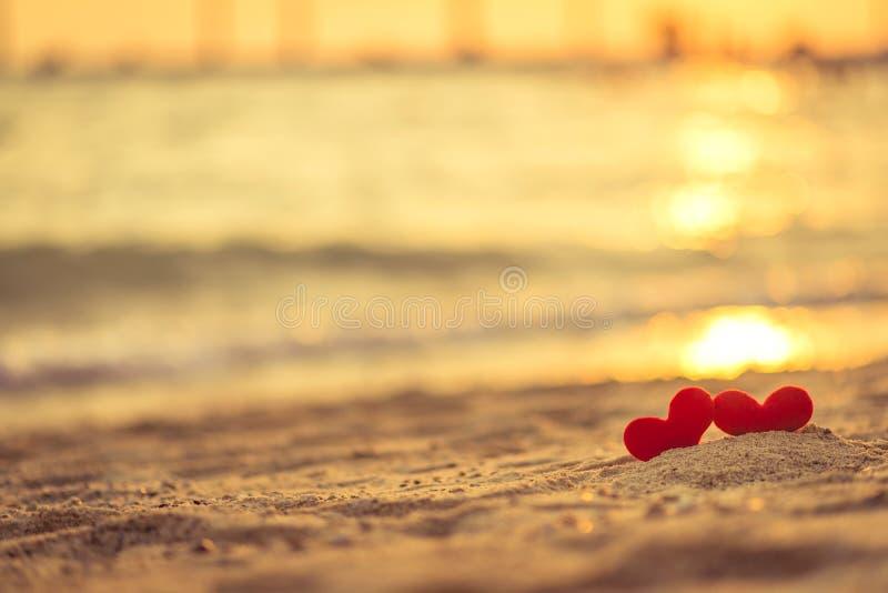 爱在情人节-在绳索垂悬的两红色心脏与日落一起 库存图片