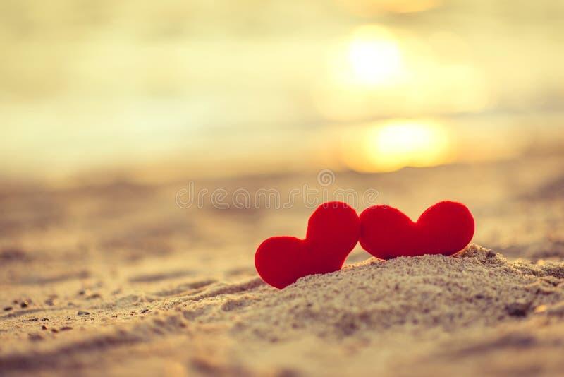 爱在情人节-在绳索垂悬的两红色心脏与日落一起 免版税图库摄影