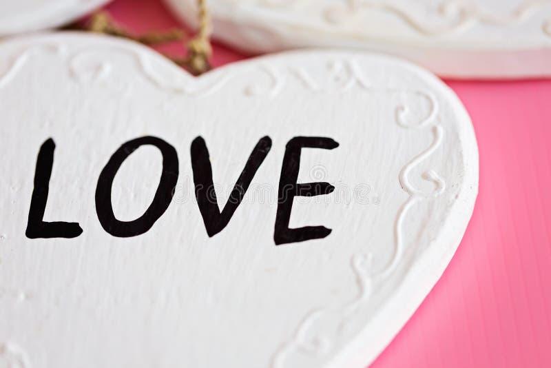 爱在桃红色背景,水平的compositi的木白色心脏 库存照片