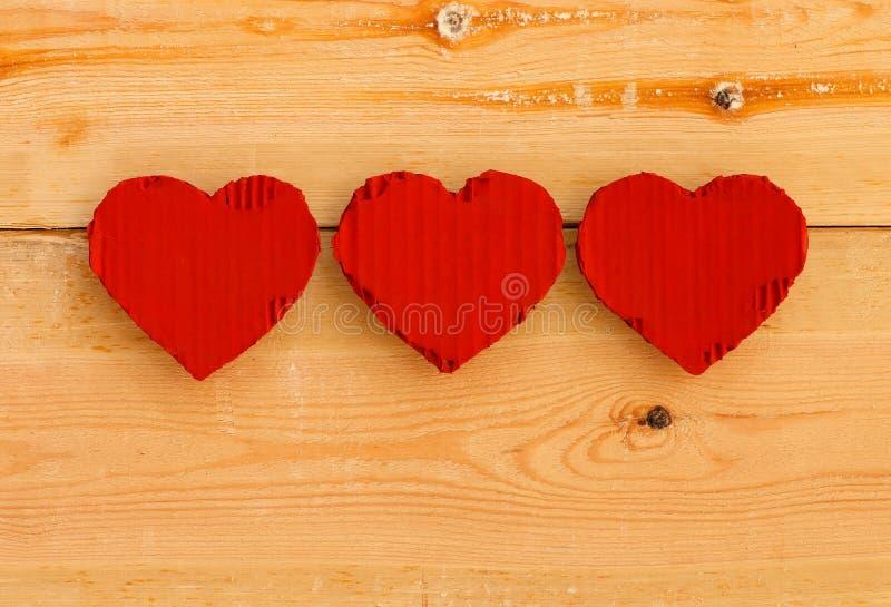 爱在概略的杉木背景的华伦泰红色纸板心脏 免版税库存图片