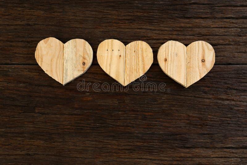 爱在概略的漂流木头背景的华伦泰木心脏 库存照片
