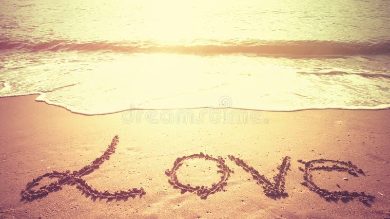 爱在海滩的沙子写的消息在早晨时间 免版税库存图片