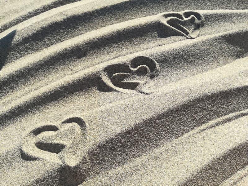 爱在海滩的沙子画的心脏 库存图片