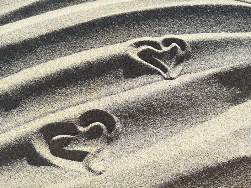 爱在海滩的沙子画的心脏 免版税库存照片