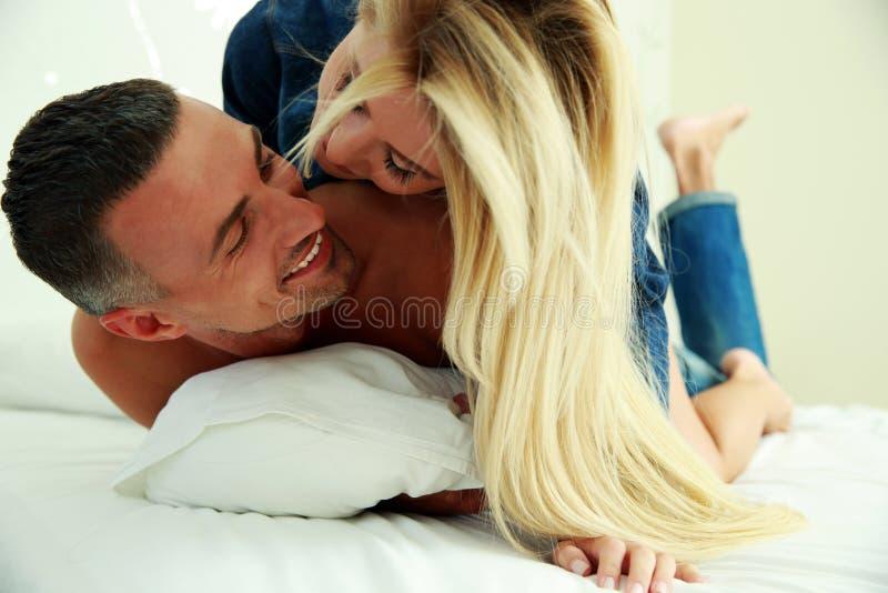 年轻爱夫妇在床上 免版税库存图片