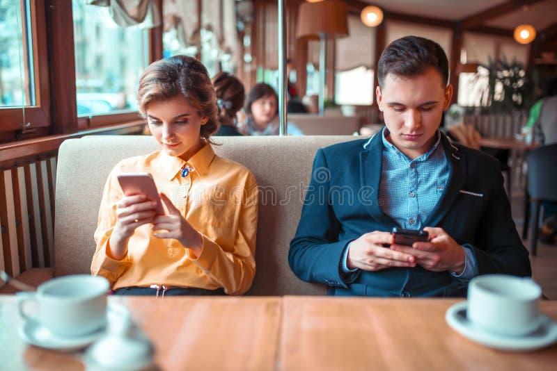 爱夫妇在餐馆使用他们的手机 免版税库存图片