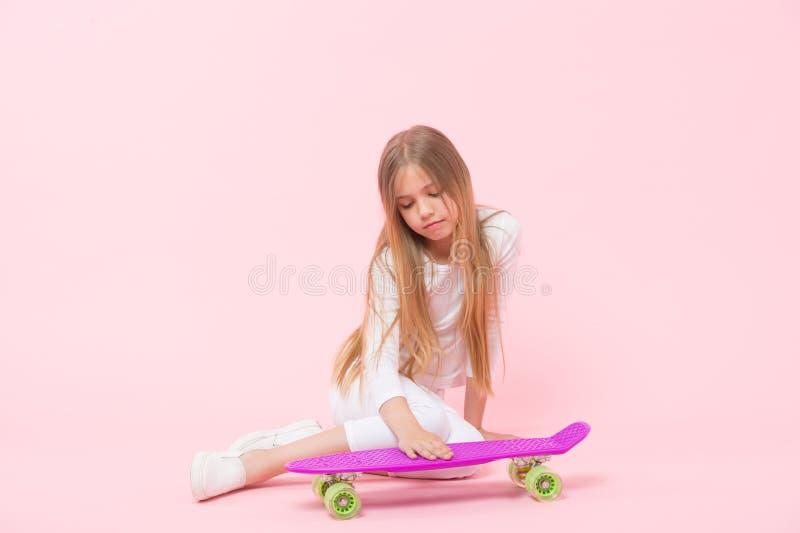 爱她的便士板 把手放的女孩在甲板上在桃红色背景上 有紫罗兰的可爱的小溜冰者 库存照片